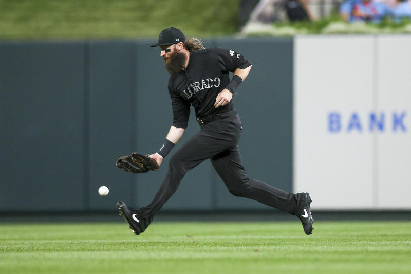 Colorado Rockies right fielder Charlie Blackmon is unable to make a catch resulting in a run being scored by St. Louis Cardinals' Dexter Fowler during the fifth inning of a baseball game Saturday, Aug. 24, 2019, in St. Louis. (AP Photo/Scott Kane)