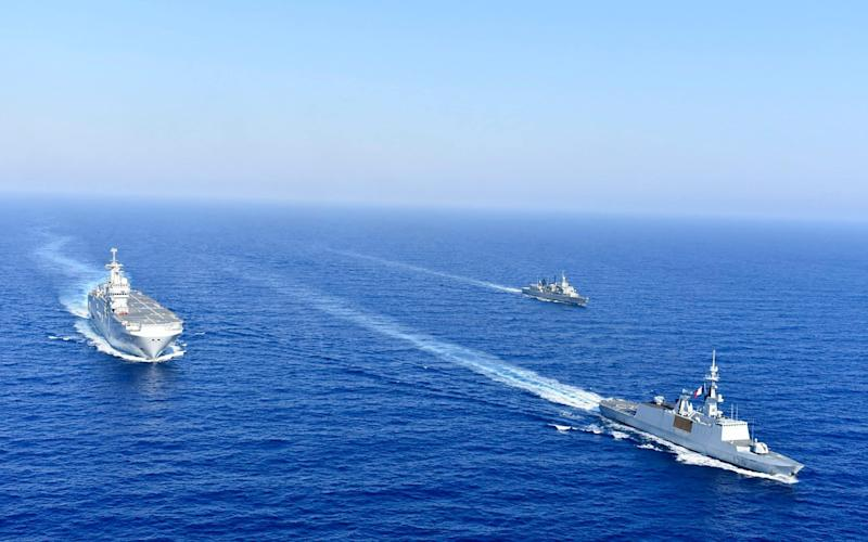 A French helicopter carrier is escorted by Greek and French warships in the eastern Mediterranean - Greek National Defence via AP)