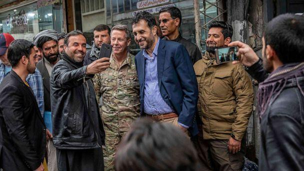 PHOTO: In this handout photo taken and released by Afghanistan's Ministry of Defence office on Feb. 26, 2020, men take selfies with their smartphones with Commander of U.S. and NATO forces in Afghanistan. (Handout via AFP/Getty Images)