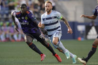 Sporting Kansas City forward Johnny Russell, right, tracks the ball with Seattle Sounders defender Abdoulaye Cissoko during the first half of an MLS soccer match, Sunday, July 25, 2021, in Seattle. (AP Photo/Ted S. Warren)