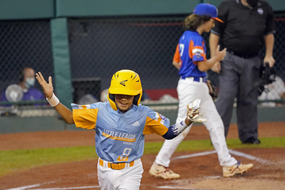 Honolulu's Kaikea Patoc-Young (9) celebrates on his way back to the dugout after scoring on a wild pitch as Taylor, Mich., pitcher Ethan Van Belle (13) walks back to the mound during the first inning of a baseball game at the Little League World Series in South Williamsport, Pa., Wednesday, Aug. 25, 2021. Hawaii won 2-0. (AP Photo/Tom E. Puskar)