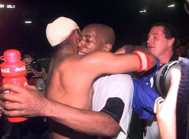 Paul Ince, left, hugs Ian Wright, right, after England's crucial goalless draw in Turin (Adam Butler/PA)