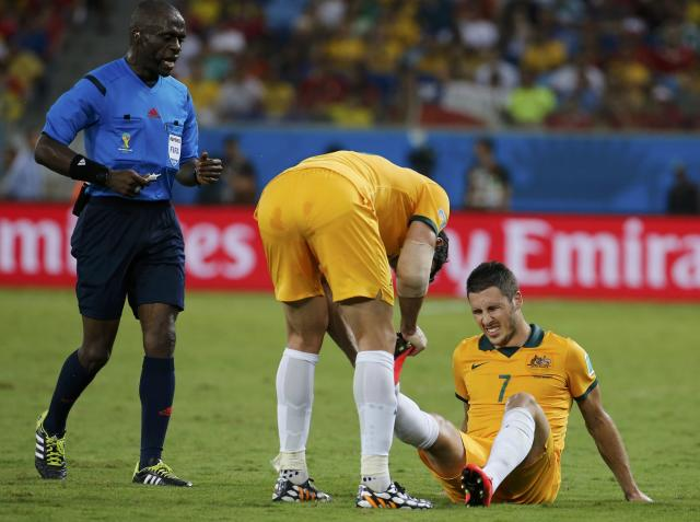 Australia's Leckie grimaces on the pitch during the team's 2014 World Cup Group B soccer match against Chile at the Pantanal arena in Cuiaba