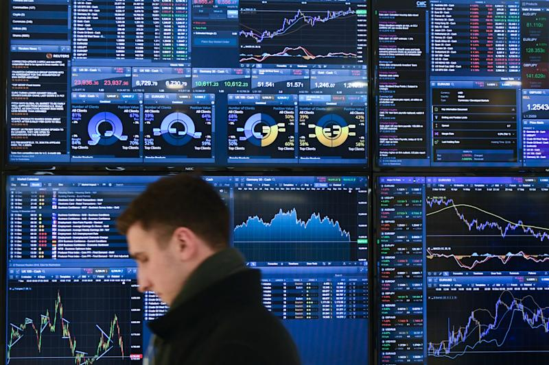 A trader walks past a display showing financial data at the offices of CMC Markets in the City of London on December 10, 2018 after Britain's Prime Minister Theresa May made a statement in the House of Commons announcing the government's intention to delay the 'meaningful' vote on the Brexit withdrawl agreement. - British Prime Minister Theresa May on December 10, 2018 postponed a parliamentary vote on her Brexit deal to avoid a crushing defeat, saying she would return to the EU for further talks in a perceived sign of weakness that sent the pound plunging. (Photo by Daniel SORABJI / AFP) (Photo credit should read DANIEL SORABJI/AFP via Getty Images)