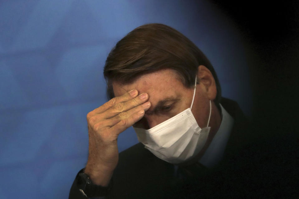Brazil's President Jair Bolsonaro, wearing protective face mask, listens during a ceremony announcing economic measures to support philanthropic hospitals and help them treat COVID-19 patients, at the Planalto Presidential Palace, in Brasilia, Brazil, Thursday, March 25, 2021. (AP Photo/Eraldo Peres)
