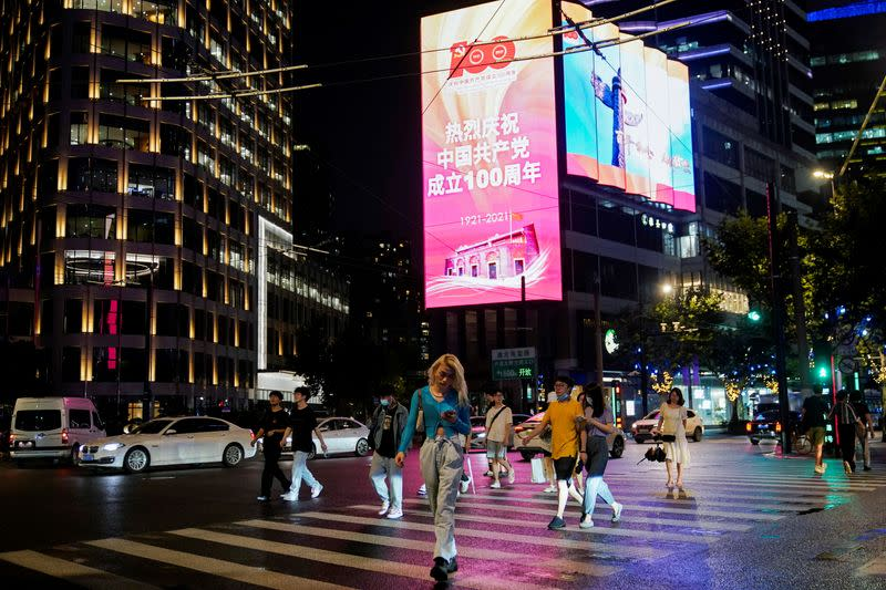 People walk on a street in front of a screen marking the 100th founding anniversary of the Communist Party of China, in Shanghai