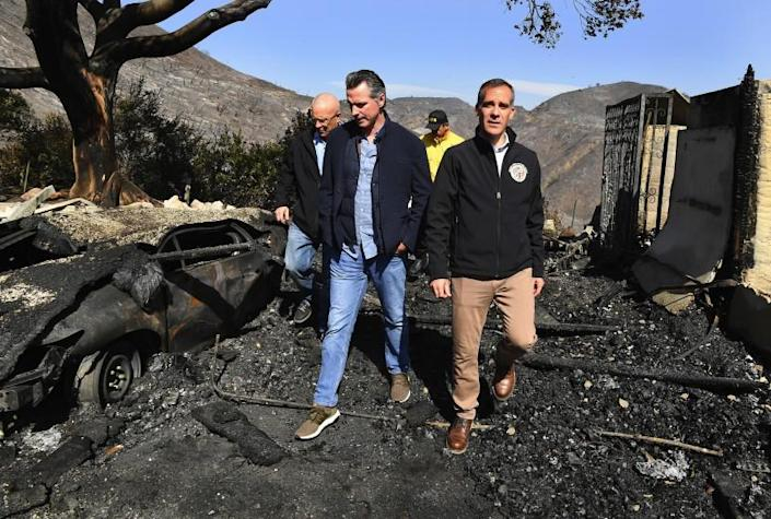Wally SkalijLos Angeles Times GOV. GAVIN NEWSOM, center, looks over the fire devastation in Brentwood with L.A. Mayor Eric Garcetti, right, and Councilman Mike Bonin, left rear. Newsom and the state face dual crises in blackouts and wildfires.
