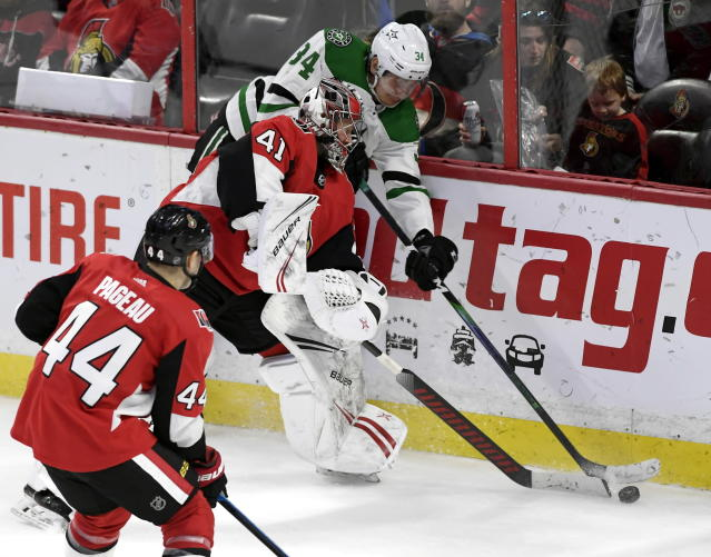 Dallas Stars right wing Denis Gurianov (34) tries to take the puck from Ottawa Senators goaltender Craig Anderson (41) behind the net during the third period of an NHL hockey game Sunday, Feb. 16, 2020, in Ottawa, Ontario. (Justin Tang/The Canadian Press via AP)