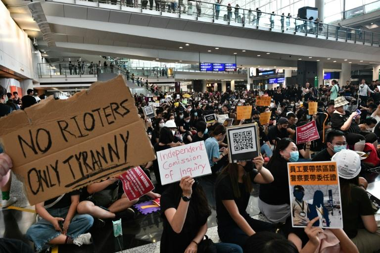 Visitors were greeted at the airport by a sea of black-clad protesters chanting anti-government slogans (AFP Photo/Anthony WALLACE)