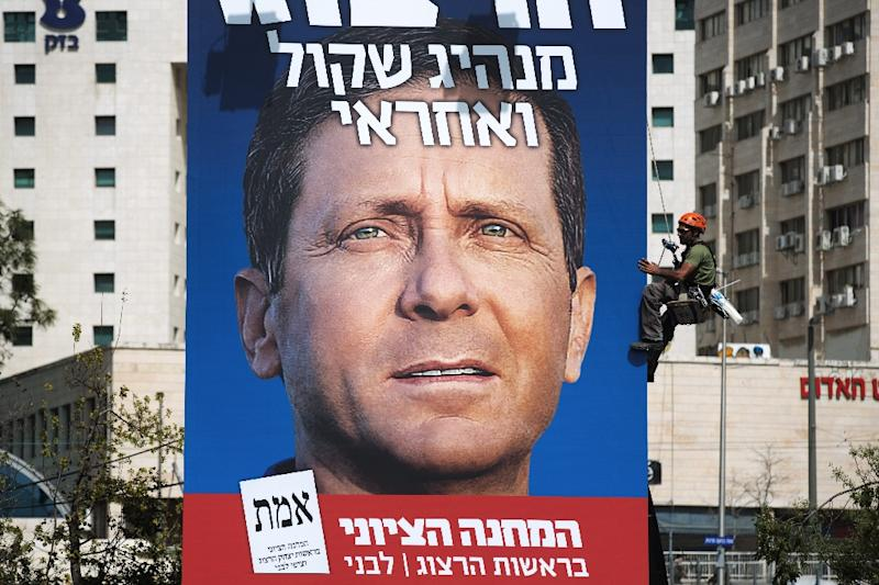 Workers hang a giant campaign poster of Israeli Labour Party leader and co-leader of the Zionist Union list for the upcoming general election, Isaac Herzog on March 11, 2015 in Jerusalem (AFP Photo/Menahem Kahana)