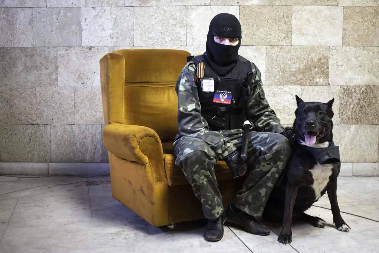 A masked pro-Russian protester sits beside a dog as he poses for a picture inside a regional government building in Donetsk, eastern Ukraine April 25, 2014. Picture taken April 25, 2014. REUTERS/Marko Djurica (UKRAINE - Tags: POLITICS CIVIL UNREST ANIMALS PORTRAIT TPX IMAGES OF THE DAY)