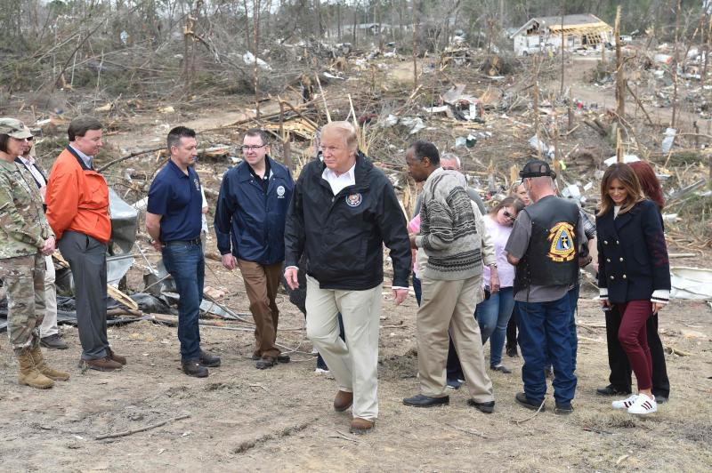 President Donald Trump tours a tornado-affected in Beauregard, Alabama, on March 8, 2019. With him are first lady Melania Trump and Ben Carson (center-right), US Secretary of Housing and Urban Development (HUD), on March 8, 2019 in Beauregard, Alabama.
