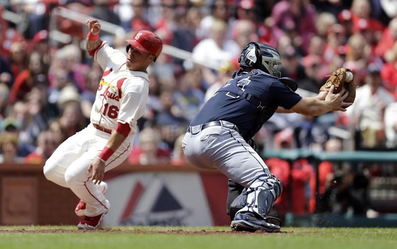 St. Louis Cardinals' Kolten Wong, left, scores as the throw gets past Atlanta Braves catcher Evan Gattis during the fourth inning of a baseball game on Saturday, May 17, 2014, in St. Louis. (AP Photo/Jeff Roberson)