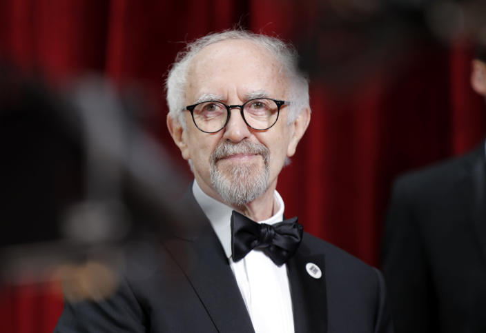 FILE - In this Sunday, Feb. 9, 2020 file photo, Jonathan Pryce arrives at the Oscars, at the Dolby Theatre in Los Angeles. Queen Elizabeth II has used her birthday honors list to celebrate the achievements of people in the limelight, as well as those at the forefront of the U.K.'s rapid rollout of coronavirus vaccines over the past few months. In the world of entertainment, actor Jonathan Pryce, who will play the queen's late husband Prince Philip in the final seasons of Netflix's royal drama The Crown, is knighted. (AP Photo/John Locher)