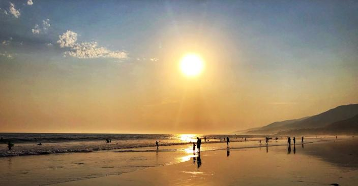 """Beachgoers sample the waves at L.A. County's Zuma Beach shortly before sunset on Saturday. <span class=""""copyright"""">(Robert Gauthier / Los Angeles Times)</span>"""