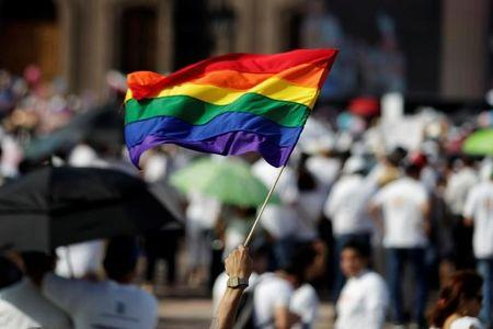 A man holds up the rainbow flag towards thousands of catholics and conservatives gathered together against the legalization of gay marriage and to defend their interpretation of traditional family values in Monterrey City, Mexico September 10, 2016. REUTERS/Daniel Becerril