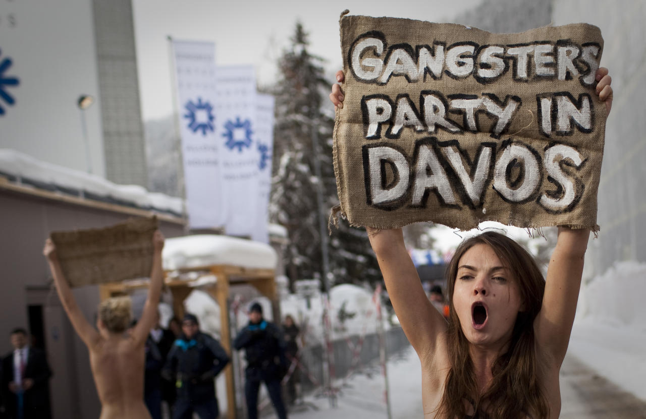 Topless Ukrainian protesters demonstrate at the entrance to the congress center where the World Economic Forum takes place in Davos, Saturday, Jan. 28, 2012. The activists are from the group Femen, which has have become popular in Ukraine for staging small, half-naked protests against a range of issues including oppression of political opposition. (AP Photo/Anja Niedringhaus)