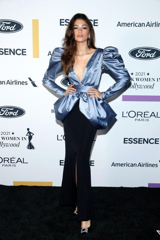 """<p>Zendaya stunned in a 1982 Yves Saint Laurent Couture gown from her stylist Law Roach's personal collection at the ESSENCE Black Women in Hollywood Awards. </p><p>Roach wrote in his <a href=""""https://www.instagram.com/p/CN_CkCrDXrV/"""" rel=""""nofollow noopener"""" target=""""_blank"""" data-ylk=""""slk:Instagram post"""" class=""""link rapid-noclick-resp"""">Instagram post</a>, showing the 24-year-old pose in the plunging, peplum, puff-sleeved blue and black gown, that the dress was previously owned by Black entrepreneur and trailblazer Eunice Johnson, noting: 'We pay homage'.</p><p>Johnson co-published Ebony magazine and founded The Ebony Fashion Fair, which highlighted and celebrated the work of Black models and designers across the United States for 50 years. </p>"""
