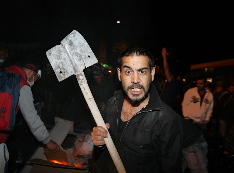 A Turkish protester holds a shovel as they prepare a barricade before clashing with riot police stationed on the John F. Kennedy Street, in front of the U. S. embassy in Turkish capital, Ankara, early Sunday, June 9, 2013. Tens of thousands of people thronged Istanbul's Taksim Square Saturday, and thousands more turned out in central Ankara as protests that have presented Turkish Prime Minister Recep Tayyip Erdogan with the first serious challenge to his leadership entered their second week.(AP Photo/Burhan Ozbilici)