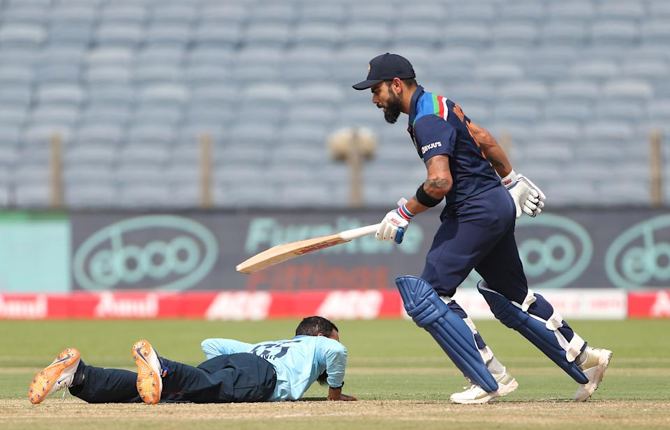 PUNE, INDIA - MARCH 26: India batsman Virat Kohli picks up some runs as England bowler Adil Rashid looks on from the floor during the 2nd One Day International between India and England at MCA Stadium on March 26, 2021 in Pune, India. (Photo by Surjeet Yadav/Getty Images)
