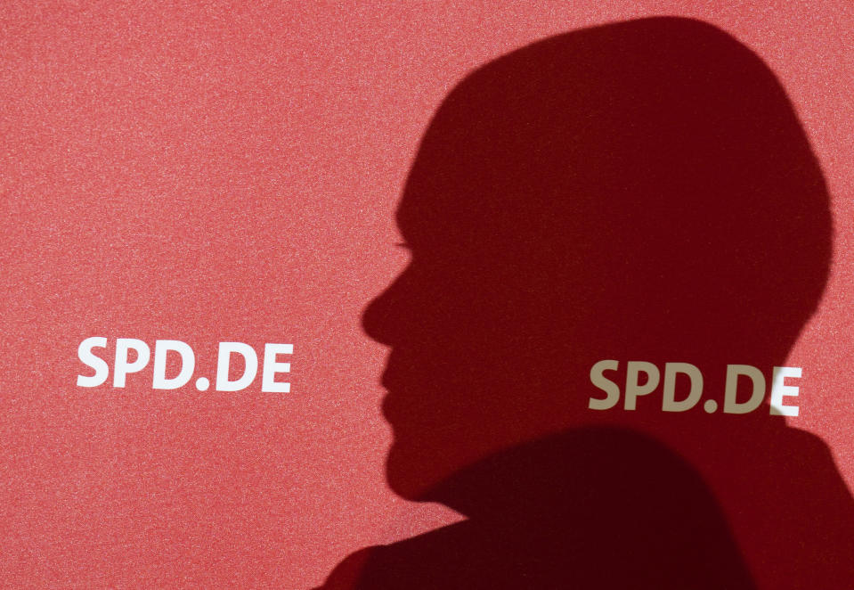 German Finance Minister and Social Democratic Party, SPD, candidate for chancellor Olaf Scholz casts his shadow on a billboard during an election campaign event named: 'Future talk with employees' in Wolfsburg, Germany, Tuesday, Sept. 21, 2021. (Julian Stratenschulte/dpa via AP)