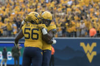 FILE - In this Sept. 14, 2019, file photo, West Virginia defensive linemen Darius Stills (56) and Dante Stills (55) hug during an NCAA college football game in Morgantown, W.Va. Dante Stills and his older brother, Darius, are among the Big 12's sack leaders and they'll be looking to cause more disruption when West Virginia hosts No. 11 Texas on Saturday. (AP Photo/Raymond Thompson, File)