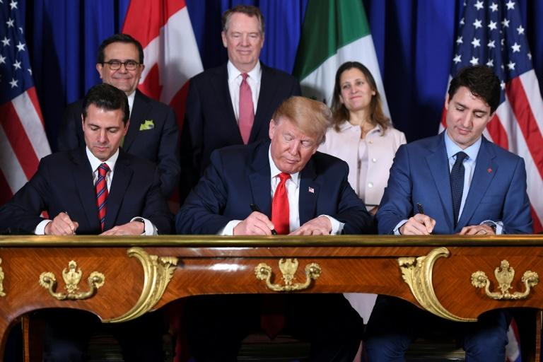 L-R: Mexico's President Enrique Pena Nieto, US President Donald Trump and Canadian Prime Minister Justin Trudeau sign a free trade agreement in Buenos Aires, in 2018