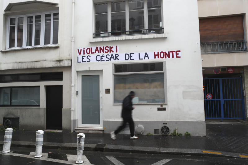 """A man walks by the Academie des Cesar headquarters where a graffiti reads """"Violanski, Cesar awards of shame"""", playing with the French word for rape and the name of Roman Polanski, Thursday, Feb. 27, 2020 in Paris. French women's rights activists are plastering banners to protest multiple nominations for Roman Polanski at the Cesar Awards ceremony, France's equivalent of the Oscars. This year's Cesars have been shaken by boycott calls since the nominations for Polanski's """"An Officer and a Spy,"""" because a French woman recently accused Polanski of raping her in the 1970s, which he denies. (AP Photo/Thibault Camus)"""