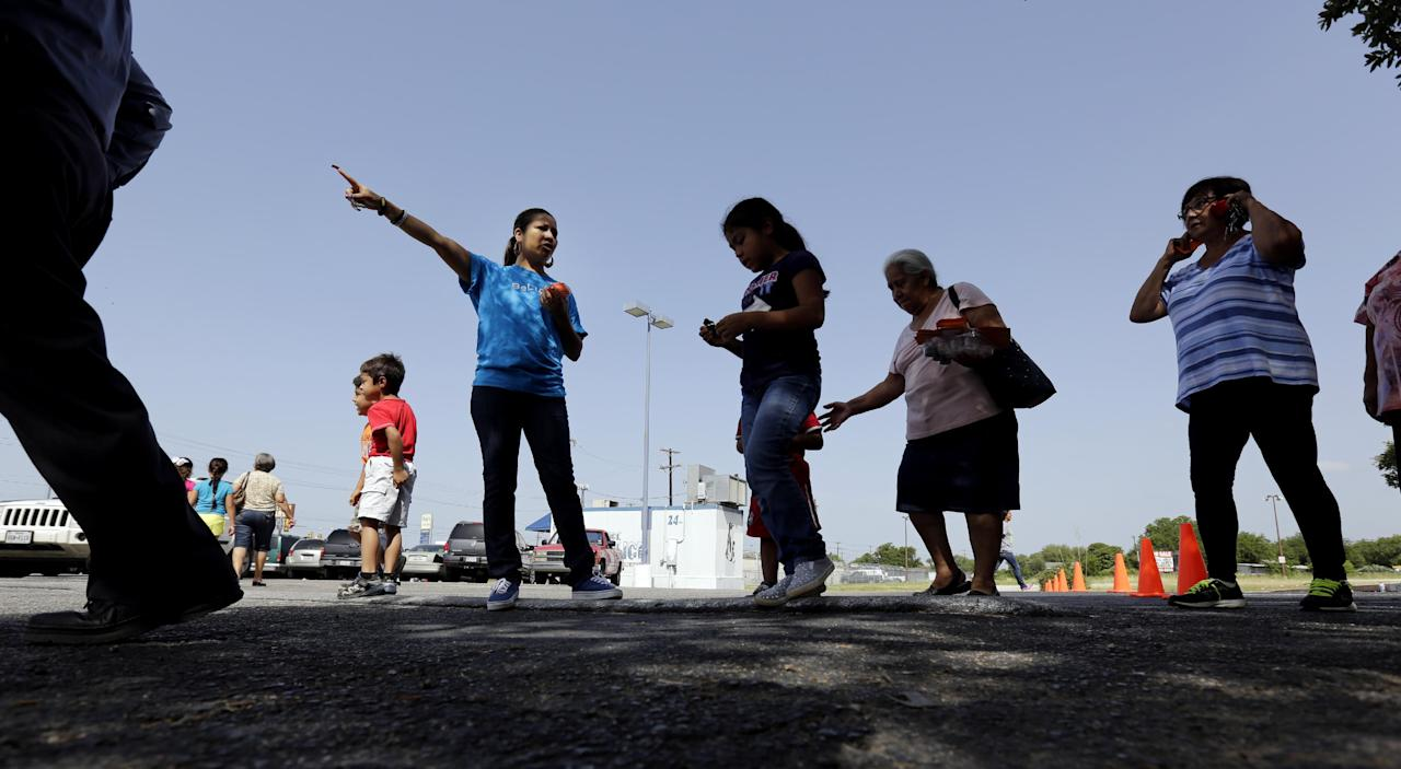 In this July 3, 2014 photo, a volunteer directs people as groceries are distributed at a food bank at the Abundant Life Church in San Antonio. The food bank is cosponsored by the Libre Initiative, partly funded by conservative billionaires Charles and David Koch, which is looking to make inroads with the rising voting block of Hispanics. (AP Photo/Eric Gay)