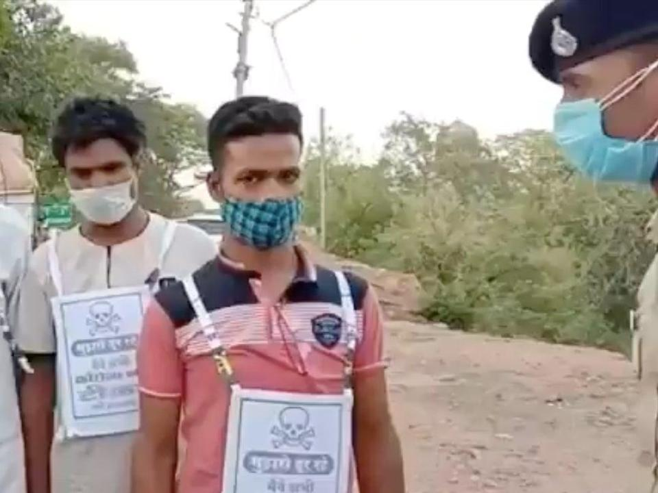 A screenshot of the video shows two men standing with a pamphlet pasted on their shirts that says 'stay away from me' (Screengrab/Video )