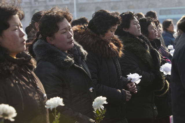 North Korean women gather on Kim Il Sung Square in Pyongyang, North Korea to lay flowers beneath portraits of the late leaders Kim Jong Il and Kim Il Sung on Tuesday, Dec. 17, 2013. Across the capital city, North Koreans observed the second anniversary of the death of Kim Jong Il. (AP Photo/David Guttenfelder)