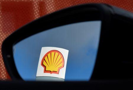 A Shell logo is seen reflected in a car's side mirror at a petrol station in west London