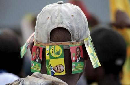 A protester wears a cap with signs of presidential candidates Moise Jean Charles and Jude Celestin during a demonstration against the preliminary results of the presidential elections in Port-au-Prince, Haiti, November 18, 2015. REUTERS/Andres Martinez Casares