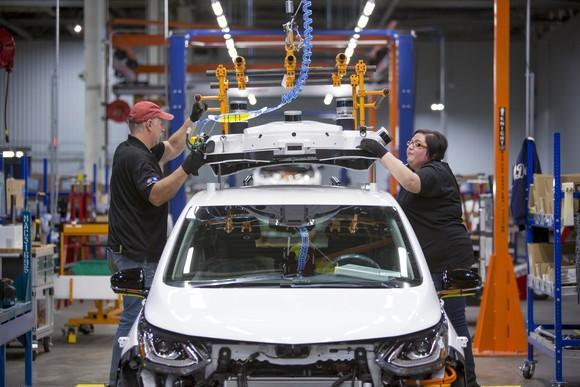 Workers at GM's Orion Assembly Plant in Orion Township, Michigan, are shown fitting a Chevrolet Bolt EV with a self-driving sensor array.