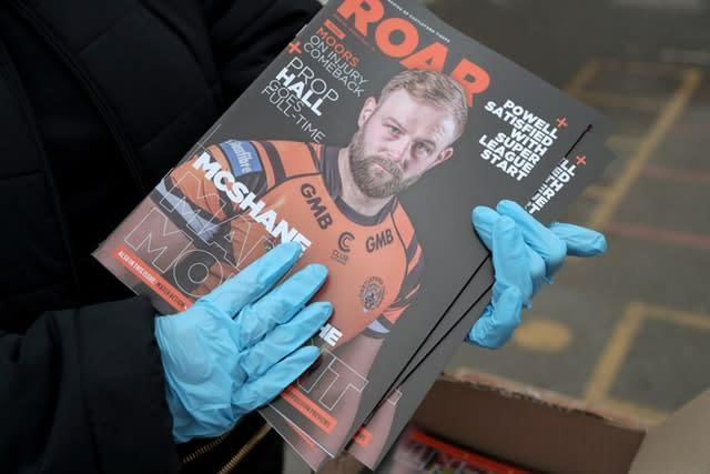 A Castleford Tigers programme seller wearing surgical gloves before the Betfred Super League match at The Mend-A-Hose Jungle, Castleford (Richard Sellers/PA)