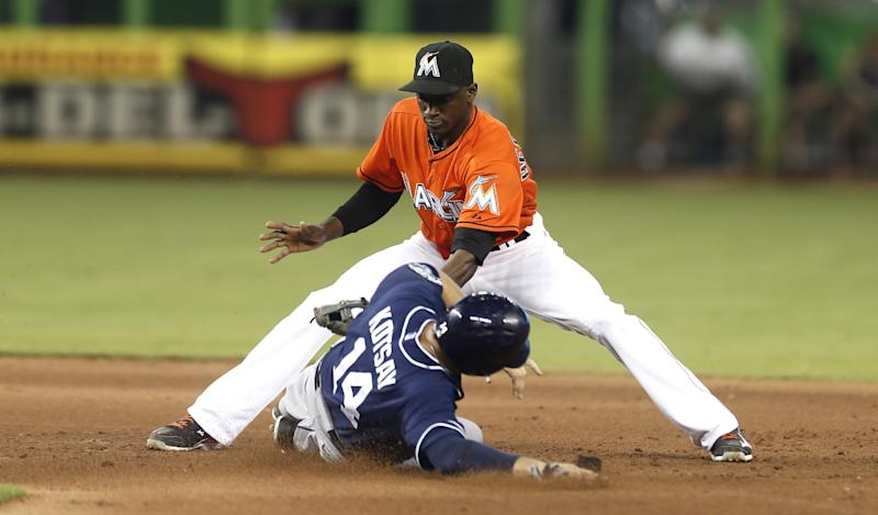 Miami Marlins shortstop Adeiny Hechvarria (3) tags San Diego Padres runner Mark Kotsay (14) out, as he tried to steal to second during the ninth inning of a baseball game in Miami, Sunday, June 30, 2013. The Marlins won 6-2 on Jeff Mathis' ninth inning grand slam home run. (AP Photo/J Pat Carter)