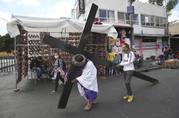 A Christian carries a cross in a reenactment of the crucifixion of Jesus Christ, in the Iztapalapa borough of Mexico City, Friday, April 2, 2021, amid the new coronavirus pandemic. Christians in Latin America mark Good Friday this year amid the coronavirus crisis with some religious sites open to limited numbers of faithful but none of the mass pilgrimages usually seen in the Holy Week leading up to Easter. (AP Photo/Marco Ugarte)