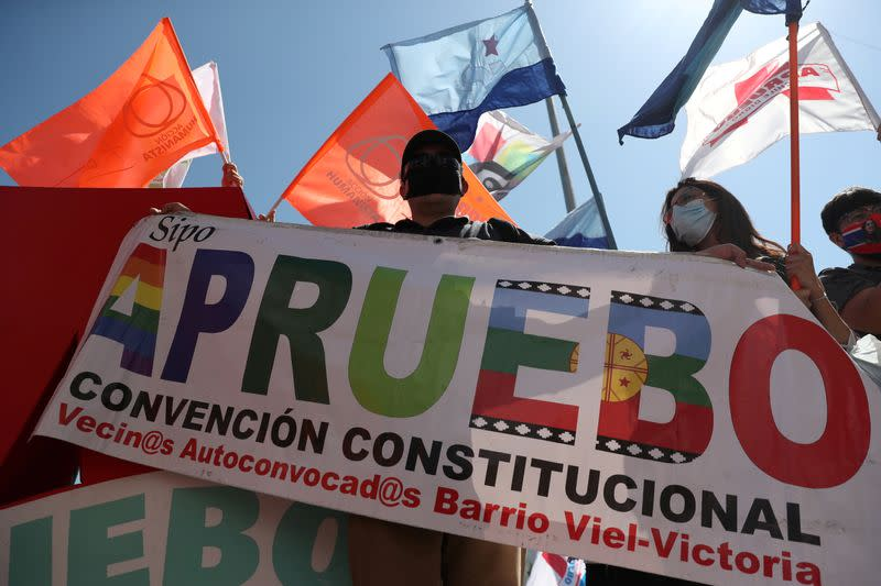 "FILE PHOTO: An activist holds a sign reading ""I approve, constitutional convention"" ahead of the upcoming referendum on a new Chilean constitution in Santiago"