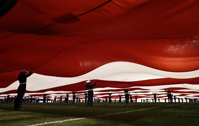 United States Marines support a 100 yard American flag during pre-game ceremonies at the Holiday Bowl NCAA college football game Monday, Dec. 30, 2013, in San Diego. (AP Photo/Gregory Bull)