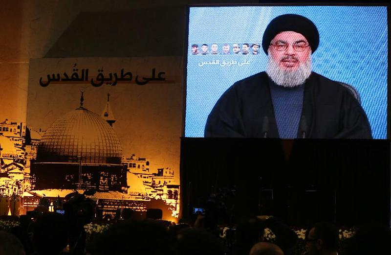 Shiite supporters watch Hassan Nasrallah, the head of Lebanon's militant Shiite Muslim movement Hezbollah, addressing them through a giant screen on January 30, 2014 in Beirut's southern suburb of Mujammaa Sayyed al-Shuhada