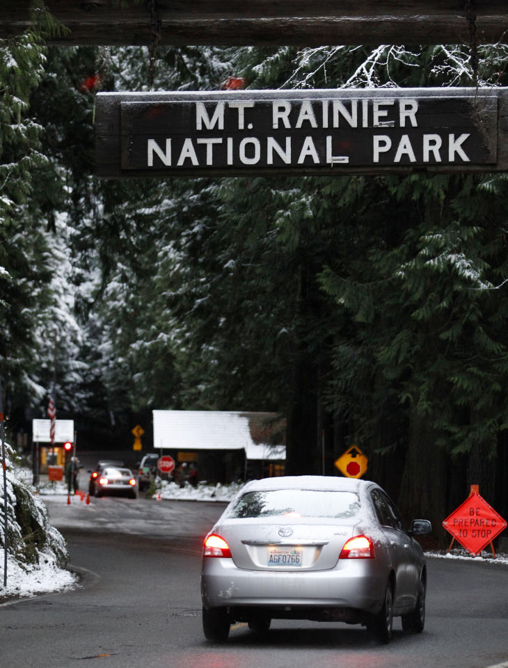 Cars approach the Nisqually entrance to Mount Rainier National Park Saturday morning, Jan. 7, 2012, near Ashford, Wash. The park opened for the first time since the shooting death of Ranger Margaret Anderson on Jan. 1. A memorial service for Anderson will be Tuesday, Jan. 10, in Tacoma, Wash. (AP Photo/Elaine Thompson)