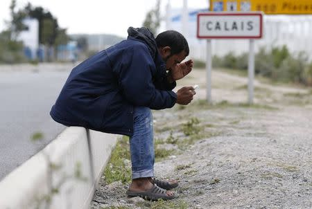A migrant looks at his mobile phone as he sits near a road sign on the main access route to the Ferry harbour Terminal in Calais, northern France, July 30, 2015.  REUTERS/Pascal Rossignol