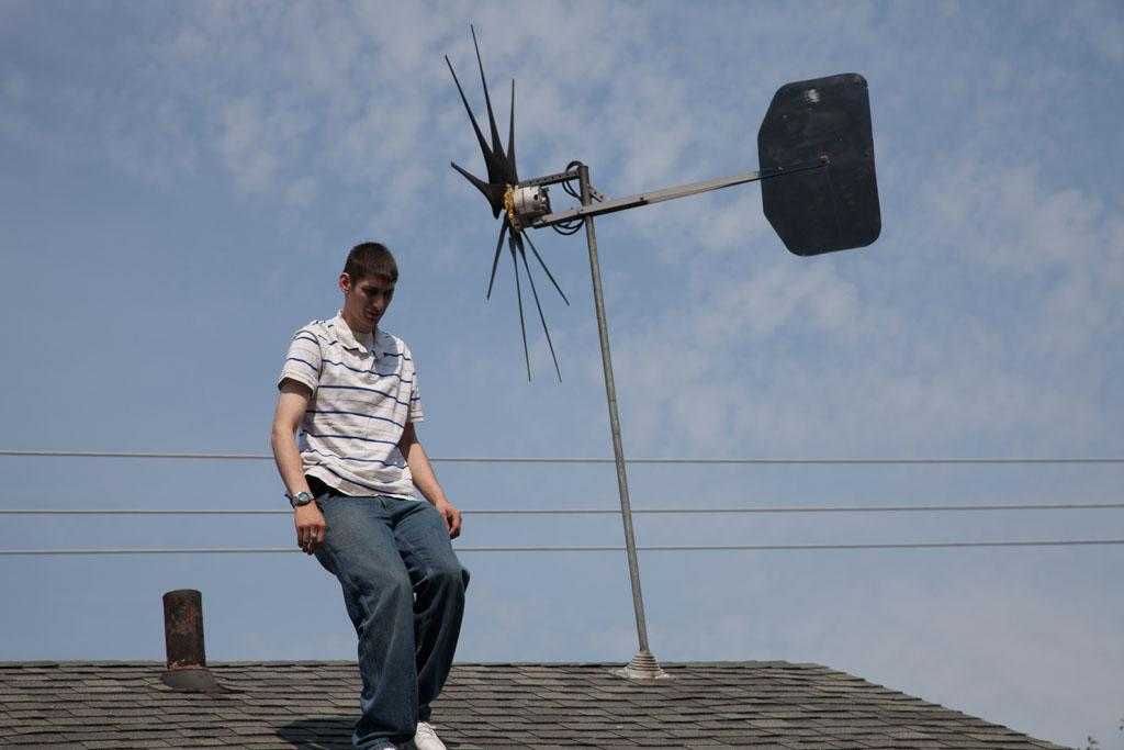 Mishawaka, IN - Bryan May adjusts the windmill on his roof.