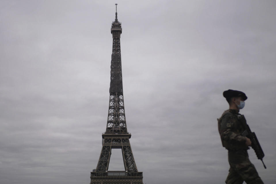 A French soldier patrols next to the Eiffel Tower in Paris, Friday, Oct. 30, 2020. France re-imposed a monthlong nationwide lockdown Friday aimed at slowing the spread of the virus, closing all non-essential business and forbidding people from going beyond one kilometer from their homes except to go to school or a few other essential reasons. (AP Photo/Thibault Camus)