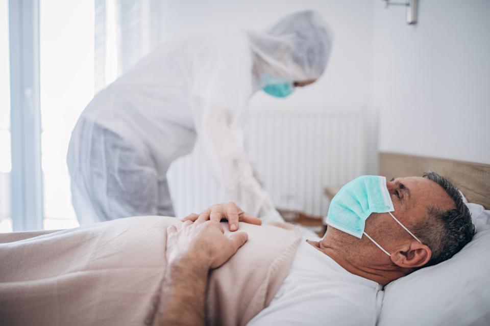 Man lying in hospital bed because of coronavirus infection, doctor is standing next to him.