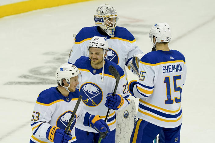 Buffalo Sabres center Sam Reinhart (23) celebrates with left wing Jeff Skinner (53), goaltender Linus Ullmark (35), and center Riley Sheahan (15) after closing the third period of an NHL hockey game against the New Jersey Devils, Saturday, Feb. 20, 2021, in Newark, N.J. (AP Photo/John Minchillo)