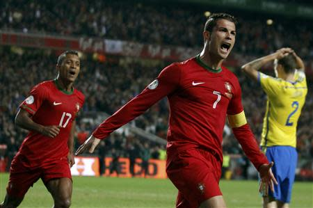 Portugal's Cristiano Ronaldo (C) celebrates beside team mate Nani after scoring a goal against Sweden during his 2014 World Cup first leg qualifying playoff soccer match at Luz stadium in Lisbon November 15, 2013. REUTERS/Rafael Marchante