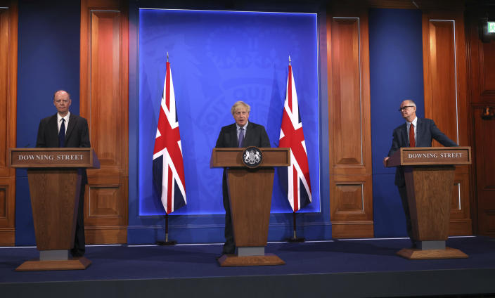 """From left, Chief Medical Officer Professor Chris Whitty, Prime Minister Boris Johnson and Chief scientific adviser Sir Patrick Vallance attend a media briefing in Downing Street, London, Monday, June 14, 2021. Johnson has confirmed that the next planned relaxation of coronavirus restrictions in England will be delayed by four weeks until July 19 as a result of the spread of the delta variant. In a press briefing Monday, Johnson said he is """"confident that we won't need more than four weeks"""" as millions more people get fully vaccinated against the virus, which could save thousands of lives. (Jonathan Buckmaster/Pool Photo via AP)"""