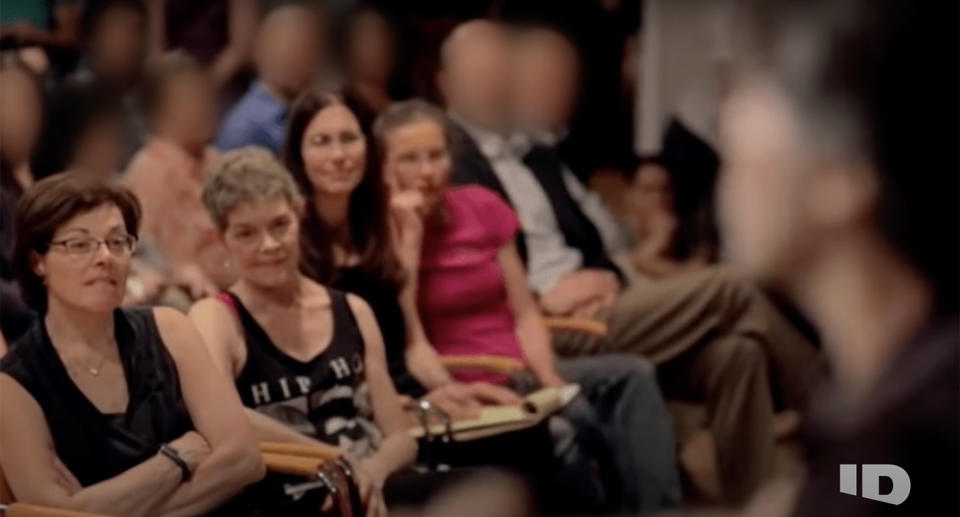 Women watch on as Keith Raneire speaks on stage. Source: YouTube/ The Lost Women of NXIVM: Rumors vs Reality