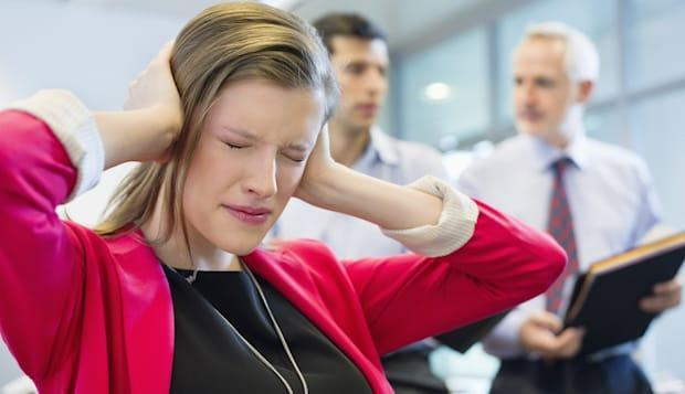 Female executive looking frustrated in an office with her colleagues discussing in the background